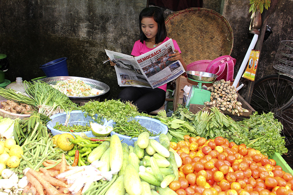 Vegetable street vendor in Yangon  reads about ­democracy