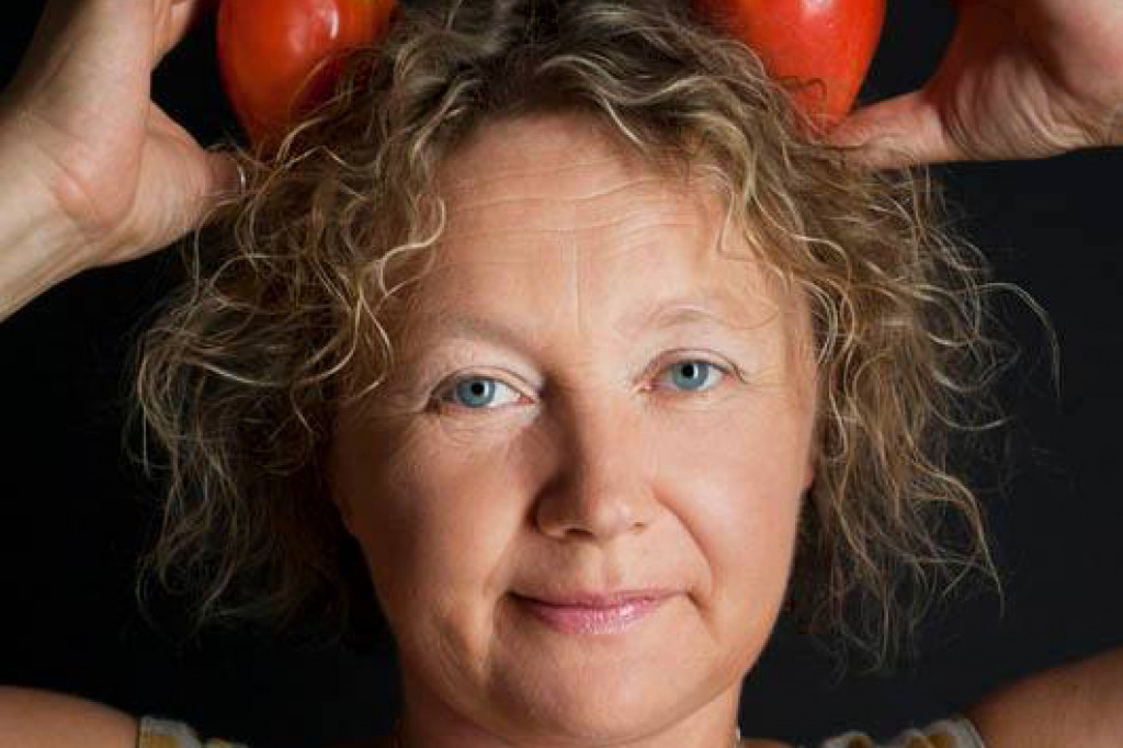 Irina Sukhy posing while holding two tomatoes in her hair.