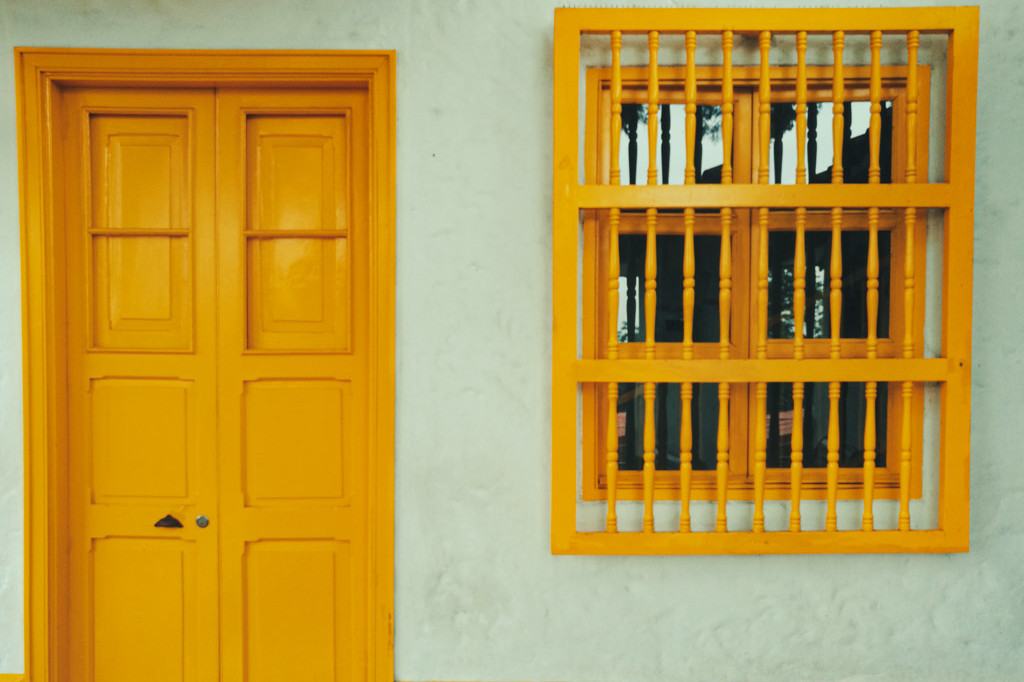 Closed yellow door with bars on the window