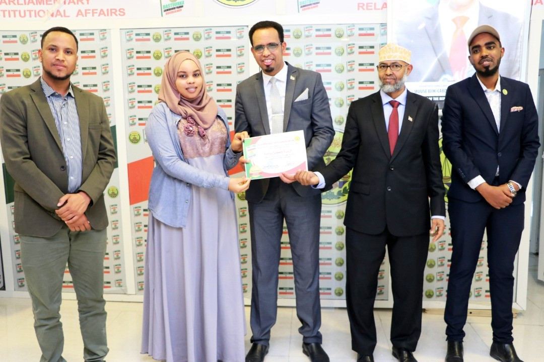Asma Saeed receives a certification of recognition for her work from the minister of parliamentary relations and constitutional affairs in Hargeisa, Somaliland.