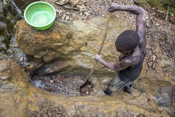 A man is digging for gold in a mine.